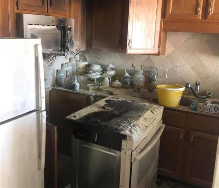 Image shows burnt stove and kitchen covered in soot.