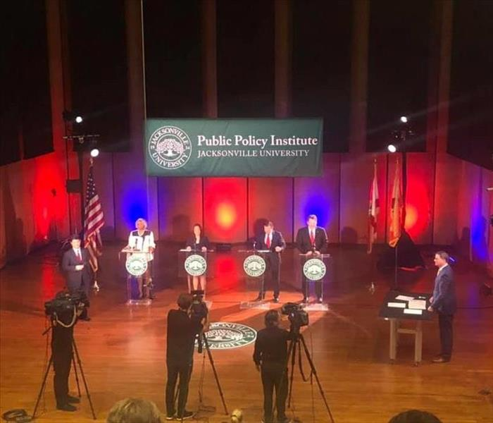 image shows politicians on stage at a debate.