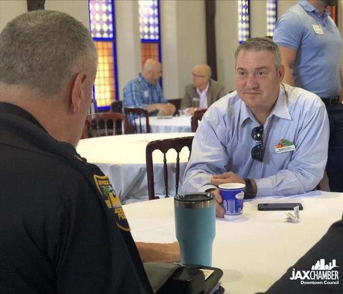 Image shows a man talking with a police officer at a breakfast event in a church.