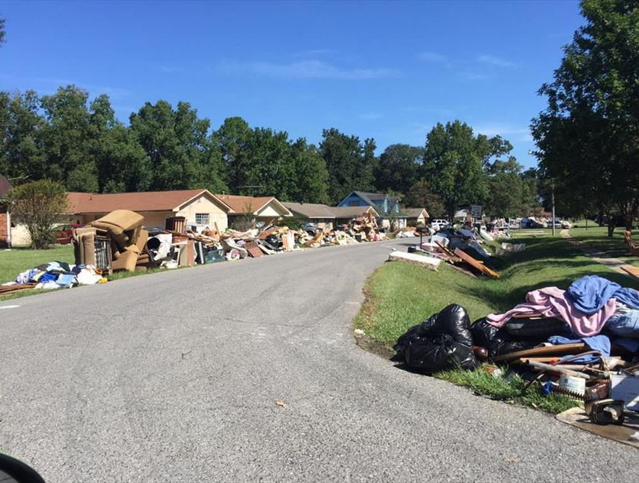 Photo shows a residential neighborhood with storm debris lining the streets.