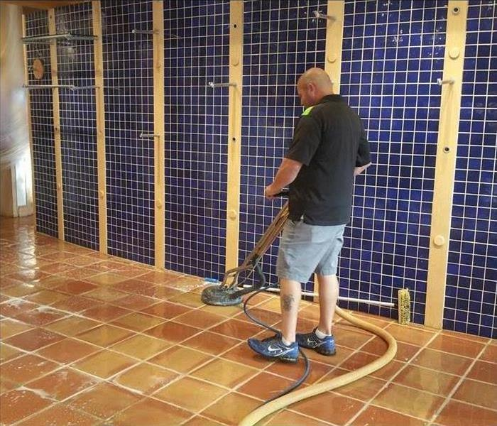 Photo shows a SERVPRO technician cleaning a clay tile floor with a spinner in a retail store.